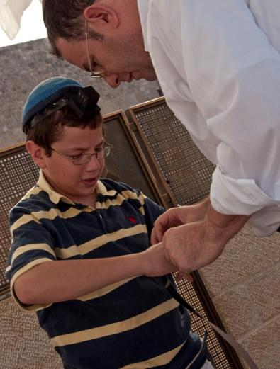 Rabbi Zvi Hirshfield helping his son put on Tefilin for the first time.