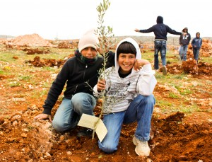Yazzen and Mahmoud planting a tree